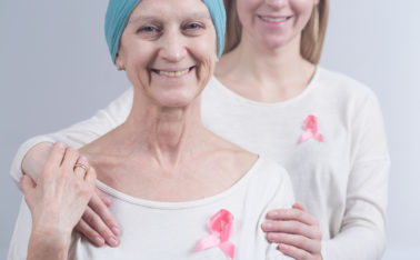 Woman after breast cancer is hugged by her close female person . Both woman have pink ribbons