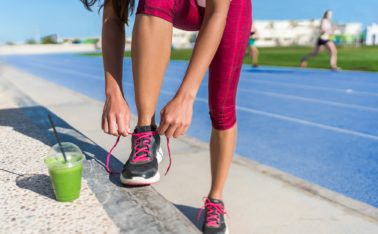 Healthy lifestyle woman runner tying running shoes drinking green smoothie cup juice drink before race workout on run tracks at outdoor stadium. Athlete getting ready for cardio training.
